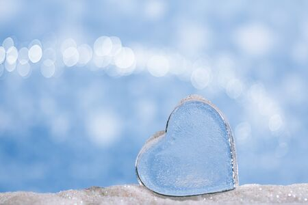 lear: clear glass heart on white  glitter and blue abstract background Stock Photo