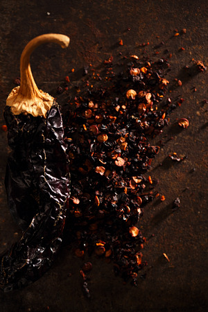 red jalapeno: chipotle - jalapeno smoked chili flakes,   and whole in iron weight bowl on old textured metal Stock Photo
