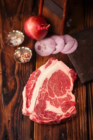 ribeye: raw beef Ribeye  steak   on wooden  table with vintage butcher cleaver knife and spices Stock Photo