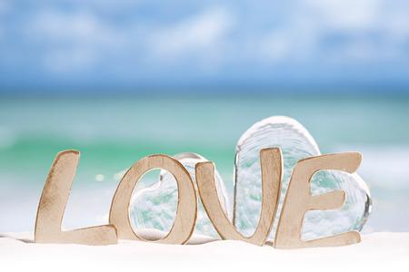 sun beach: love message and glass hearts on  beach under the sun light with  ocean , beach and seascape, shallow dof Stock Photo