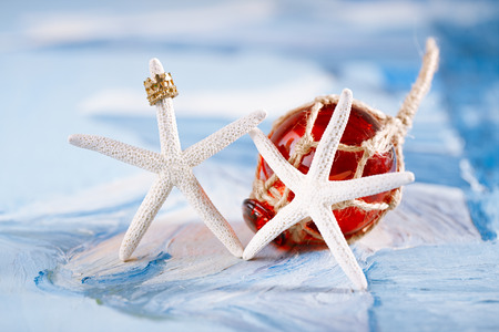 buoyant: white starfish with red Glass float on blue painted background