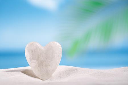 crystal heart: white crystal heart on white sand beach, ocean,  sky and seascape Stock Photo