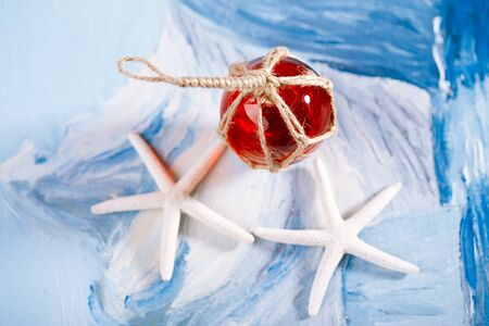 float: white starfish with red Glass float on blue painted background
