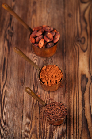 fairtrade: grated chocolate, powder and cocoa beans in vintage measuring copper pans  on old wooden background