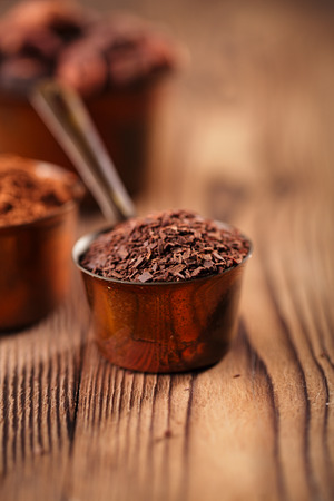 chocolate powder: grated chocolate, powder and cocoa beans in vintage measuring copper pans  on old wooden background