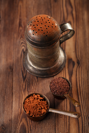 fairtrade: vintage sifter with cocoa powder and grated chocolate  in vintage measuring copper pans  on old wooden background