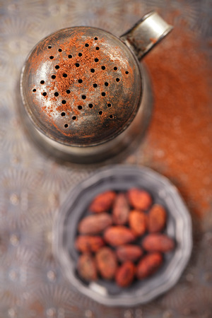 sifter: vintage sifter with cocoa beans on old backing metal background Stock Photo