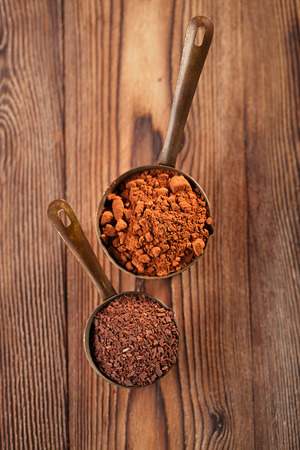 fairtrade: grated chocolate and cocoa powder  in vintage measuring copper pans  on old wooden background Stock Photo