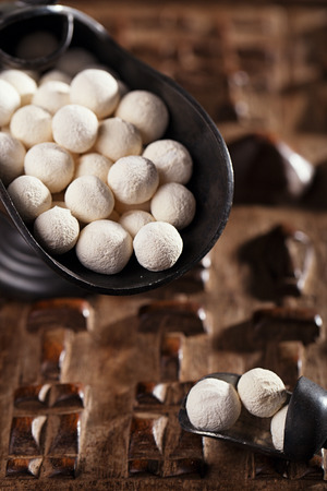 soured: kurt kurut - asian dried yogurt balls on carved wooden background