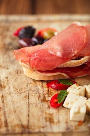 cured: Cured Meat and ciabatta bread on wooden board on background