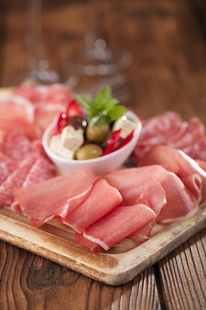 cold cuts: meat platter of Cured Meat and olives on old wooden board