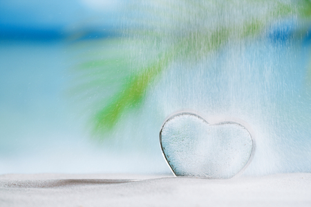 winter escape: clear glass heart and pouring sand on white sand beach, ocean,  sky and seascape Stock Photo