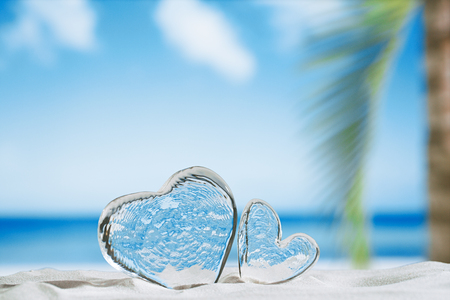 winter escape: clear glass hearts on white sand beach, ocean,  sky and seascape