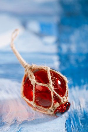 float: red Glass float on blue painted background