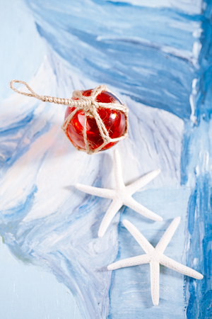 beachcombing: white starfish with red Glass float on blue painted background