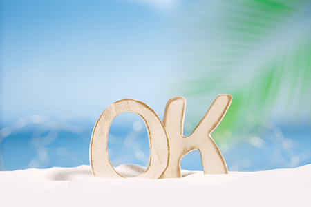 winter escape: OK word wooden letters with  ocean , beach and seascape, shallow dof Stock Photo