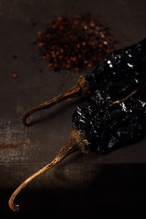 chiles secos: chipotle - jalapeno smoked chili flakes and whole on metal background