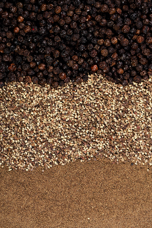 spicy cooking: whole, crashed and ground black peppercorns background