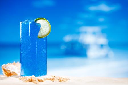 granizados: azul bebida del hielo granizado en vidrio en el fondo de la playa del mar