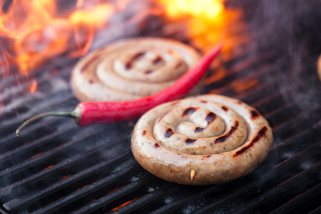 barbequing: cumberland sausage, spiral pork sausage on bbq grill with flame, homemade