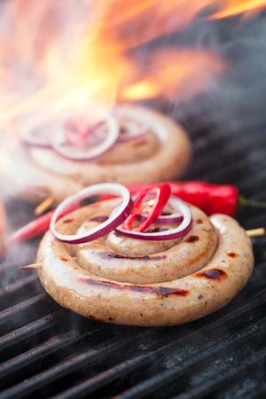 pork sausage: cumberland sausage, spiral pork sausage on bbq grill with flame, homemade