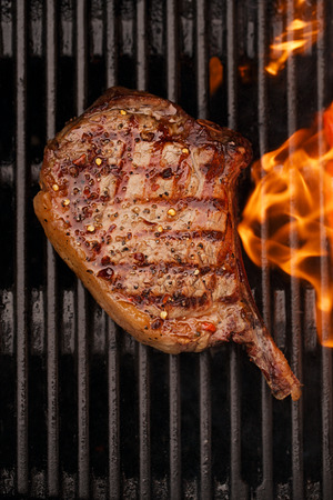 barbequing: food meat - beef steak on bbq barbecue grill with flame. Shallow dof.