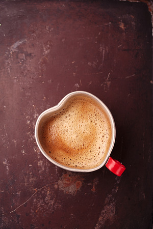 hot coffees: coffee in unusual vintage tin mug with red handle on old metal backdrop in heart shape Stock Photo