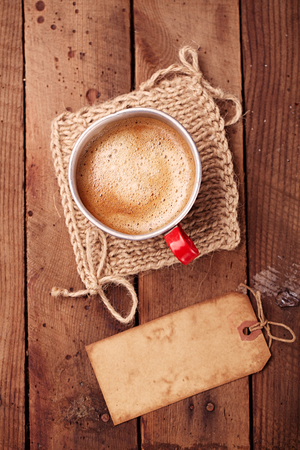 hot coffees: coffee in unusual vintage tin mug with grunge paper tag on old wood