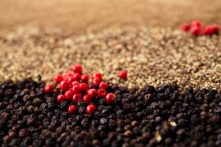 crashed: whole, crashed and ground black and red peppercorns background