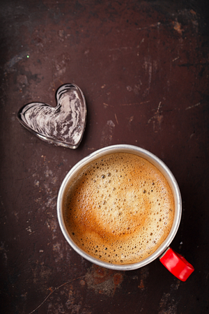 hot coffees: coffee in unusual vintage tin mug with red handle on old metal backdrop with glass heart
