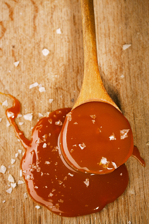 salted caramel in old wooden spoon Stockfoto