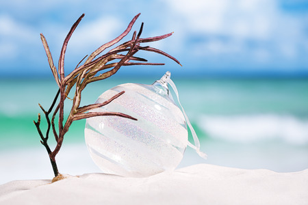 beach scene: christmas glass ball on white sand beach with seascape background Stock Photo