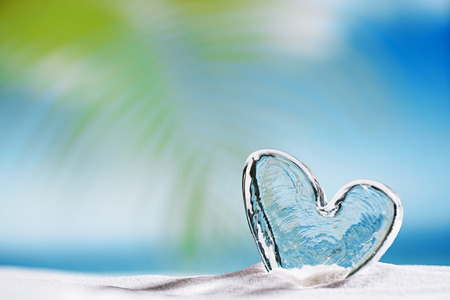 playa: clear glass heart on white sand beach, ocean,  sky and seascape