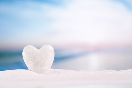 winter escape: white crystal heart on white sand beach, ocean,  sky and seascape Stock Photo