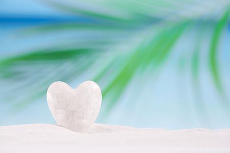 heart in sand: white crystal heart on white sand beach, ocean,  sky and seascape Stock Photo