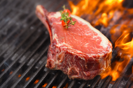 barbecue: food meat - beef steak on bbq barbecue grill with flame. Shallow dof.