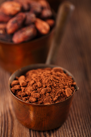 fairtrade: cocoa powder and grated chocolate  in vintage measuring copper pans  on old wooden background Stock Photo