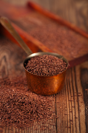 fairtrade: grated dark chocolate in copper measure pan on wooden background