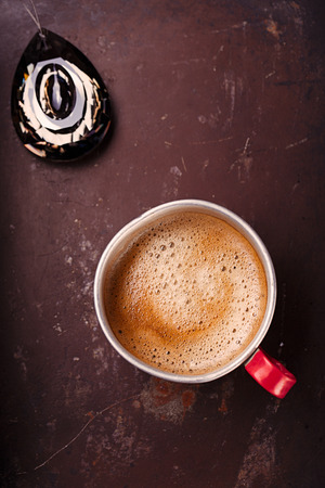 hot coffees: coffee in unusual vintage tin mug with red handle on old metal backdrop with crystal drop