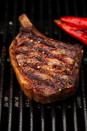 barbequing: food meat - beef steak on bbq barbecue grill no flame. Shallow dof.