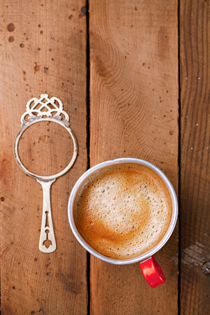 hot coffees: coffee in unusual vintage tin mug with red handle on old metal backdrop Stock Photo