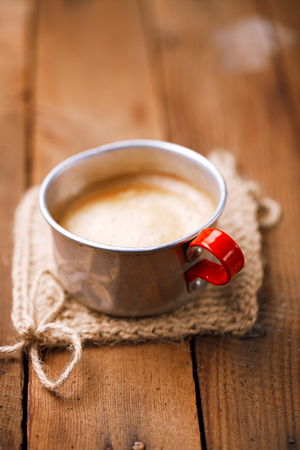 hot coffees: coffee in unusual vintage tin mug with red handle on old wood Stock Photo