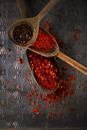 pepper flakes: red hot chillies pepper flakes in vintage wooden spoons on textured metal background Stock Photo
