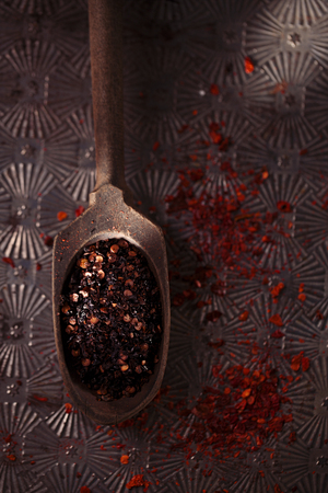 smoked: chipotle - jalapeno smoked chili flakes and red hot chillies pepper flakes in vintage wooden spoons on textured metal background