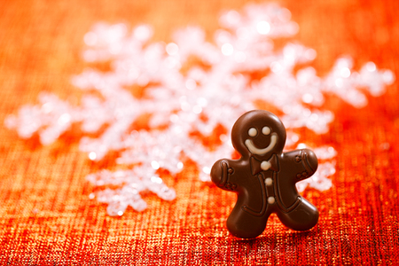 dark chocolate gingerbread man with red christmas background Stock Photo