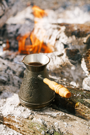 Making coffee in the fireplace  on camping or hiking in the nature Stock Photo