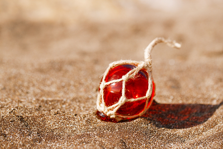 red Glass float on beach sand Stock Photo