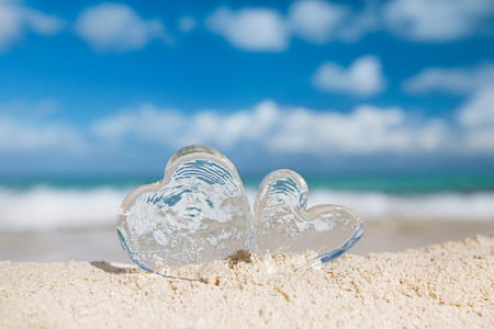 two clear glass hearts on white sand beach, ocean,  sky and seascape Stock Photo