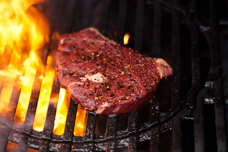 ribeye rib eye roast beef steak on bbq barbecue grill with flame. Shallow dof.
