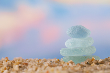 sea glass tower on  beach sand  with sunrise seascape background